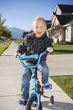 了解的小男孩乘坐有培训轮子的一辆自行车 免版税库存图片