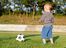 了解的小男孩踢足球 免版税库存图片