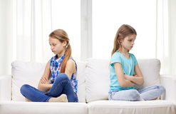 争吵的小女孩在家坐沙发 免版税库存图片