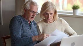 争执严肃的资深成熟的夫妇拿着检查财务的纸票据 股票视频