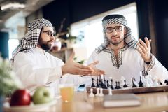 争论两个阿拉伯的商人下棋在桌上在旅馆客房 免版税图库摄影