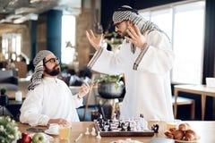 争论两个阿拉伯的商人下棋在桌上在旅馆客房 免版税库存照片