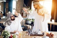 争论两个阿拉伯的商人下棋在桌上在旅馆客房 库存图片