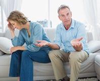 争论中部变老了夫妇坐有人gesturi的长沙发 库存图片