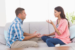 争论的夫妇,当坐沙发时 库存图片
