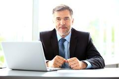 事务、人们和技术概念-与便携式计算机办公室的愉快的微笑的商人 免版税库存照片