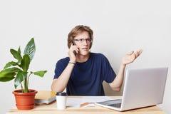 事务、办公室和技术概念 繁忙的男性enterpreneur打手势有与商务伙伴的交谈在聪明的响度单位 免版税库存照片