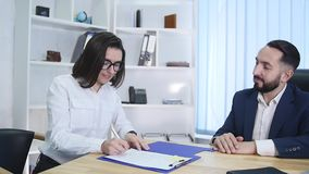 事务、合作、合作、成交和人概念-男人和妇女签署的合同和握手在办公室 股票录像