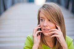 事务、技术和人概念-有智能手机的严肃的女实业家谈话在办公楼 库存图片