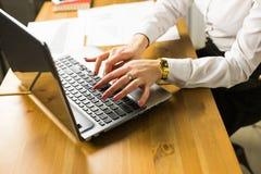 事务、教育、人们和技术概念-接近有膝上型计算机估计的女性手在桌上 图库摄影