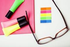 事务、教育和技术概念-接近笔记本,纸贴纸,书写在白色的另外材料 免版税库存图片