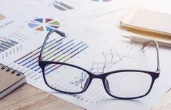 事务、glasess和纸报告关于一张木桌 事务c 免版税库存图片