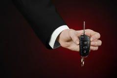 事务和礼物题材:一套黑衣服的汽车推销员把握关键到在深红背景的一辆新的汽车在演播室 库存图片