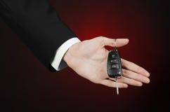 事务和礼物题材:一套黑衣服的汽车推销员把握关键到在深红背景的一辆新的汽车在演播室 免版税库存图片