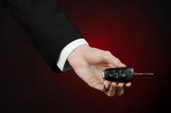 事务和礼物题材:一套黑衣服的汽车推销员把握关键到在深红背景的一辆新的汽车在演播室 免版税库存照片