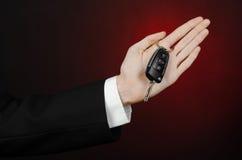 事务和礼物题材:一套黑衣服的汽车推销员把握关键到在深红背景的一辆新的汽车在演播室 图库摄影