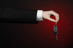 事务和礼物题材:一套黑衣服的汽车推销员把握关键到在深红背景的一辆新的汽车在演播室 免版税图库摄影