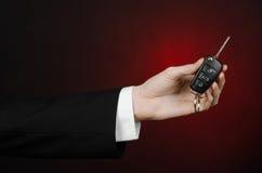 事务和礼物题材:一套黑衣服的汽车推销员把握关键到在深红背景的一辆新的汽车在演播室 库存照片