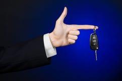 事务和礼物题材:一套黑衣服的汽车推销员把握关键到在深蓝背景的一辆新的汽车在演播室 免版税库存照片
