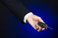 事务和礼物题材:一套黑衣服的汽车推销员把握关键到在深蓝背景的一辆新的汽车在演播室 免版税库存图片