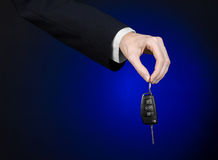 事务和礼物题材:一套黑衣服的汽车推销员把握关键到在深蓝背景的一辆新的汽车在演播室 图库摄影