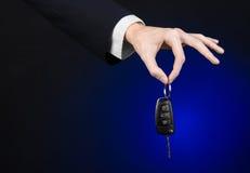事务和礼物题材:一套黑衣服的汽车推销员把握关键到在深蓝背景的一辆新的汽车在演播室 免版税图库摄影