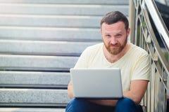 事务和自由 现代商人,有一个胡子的一个人在自然的一台膝上型计算机后是在步和赛跑 免版税图库摄影