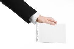 事务和记者题目:一位新闻工作者的手拿着有一支铅笔的一套黑衣服的一个笔记本在白色背景 免版税库存图片