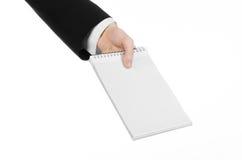 事务和记者题目:一位新闻工作者的手拿着有一支铅笔的一套黑衣服的一个笔记本在白色背景 免版税库存照片