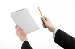 事务和记者题目:一位新闻工作者的手拿着有一支铅笔的一套黑衣服的一个笔记本在白色背景 免版税图库摄影