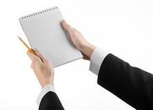 事务和记者题目:一位新闻工作者的手拿着有一支铅笔的一套黑衣服的一个笔记本在白色背景 库存照片