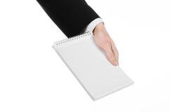 事务和记者题目:一位新闻工作者的手拿着有一支铅笔的一套黑衣服的一个笔记本在白色背景 图库摄影