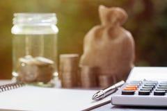 事务和财政计划概念储蓄和投资的 在笔记本、计算器和被弄脏的金钱的黑笔在瓶子,堆 免版税库存照片