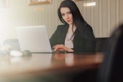 事务式衣裳的年轻可爱的情感女孩在书桌坐一个膝上型计算机和电话在办公室或观众席 库存图片