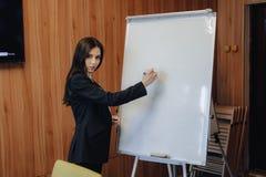 事务式衣裳的年轻情感可爱的女孩与在现代办公室或观众的flipchart一起使用 库存图片