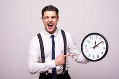 事务的叫喊的人给举行和指向在白色背景的时钟穿衣 库存图片