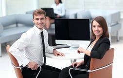 事务的微笑的成员合作坐在书桌 免版税库存照片