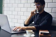 事务的成熟业主在一件黑衬衣的有与伙伴的交谈通过电话 免版税库存照片