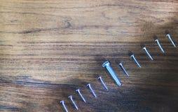 事务的概念是最小的,象一个小组在木背景的螺丝,并且螺栓不是象休息A被绘的光 库存图片