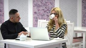 事务谈妇女和人一个咖啡馆的与膝上型计算机 影视素材