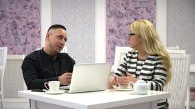 事务谈妇女和人一个咖啡馆的与膝上型计算机 股票录像