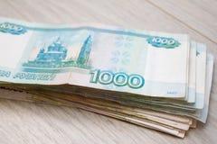 事务,财务,挽救,银行业务概念-接近的捆绑金钱俄国钞票在木桌上的一千卢布 免版税图库摄影
