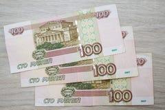事务,财务,挽救,银行业务概念-接近的捆绑金钱俄国钞票在木桌上的一百卢布 免版税库存图片