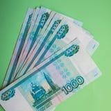事务,财务,挽救,银行业务,概念-捆绑的关闭金钱俄国钞票在绿色背景的一千卢布 库存照片
