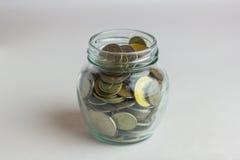 事务,财务,投资,节约金钱-在玻璃瓶子的硬币在桌上 图库摄影