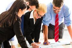 事务-办公室工作的人们作为队 库存图片