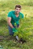 从事园艺为社区的愉快的年轻人 库存照片