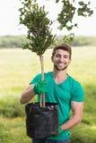 从事园艺为社区的愉快的年轻人 免版税库存图片