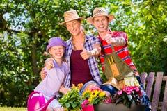 从事园艺在庭院里的家庭 免版税库存照片