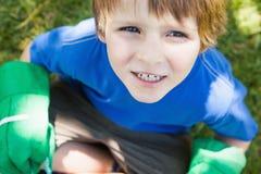 从事园艺的手套的年轻男孩在公园 库存照片